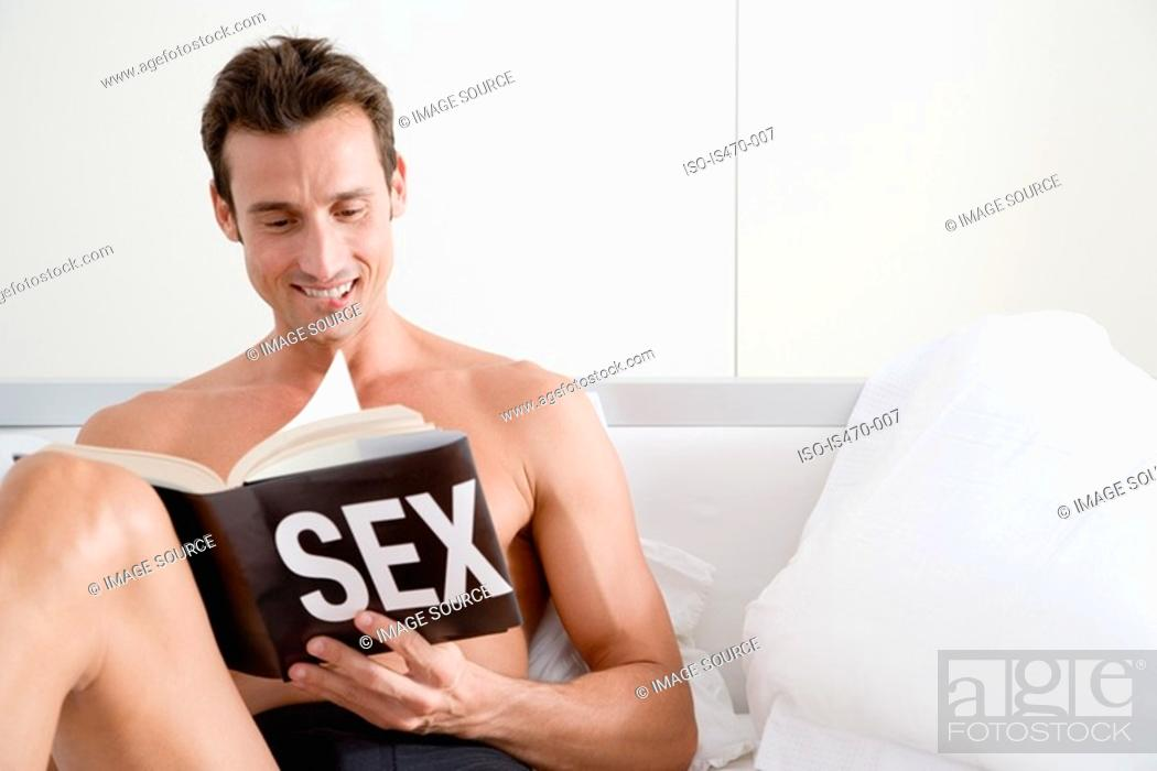 Stock Photo: Man reading a book about sex.