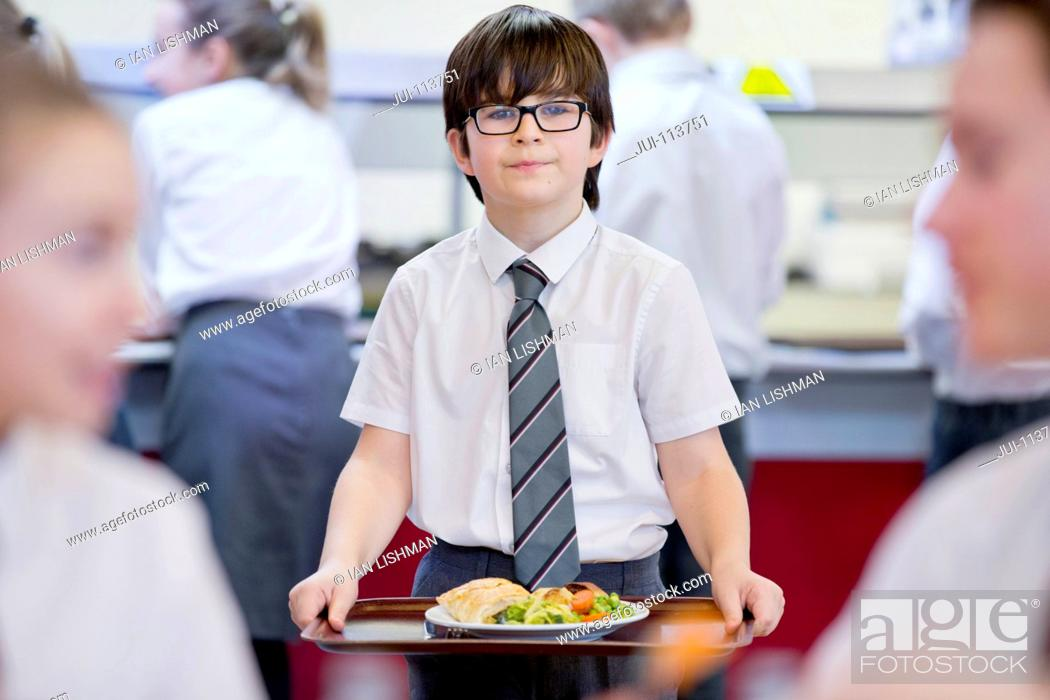 Stock Photo: Portrait smiling middle school student carrying lunch tray in school cafeteria.