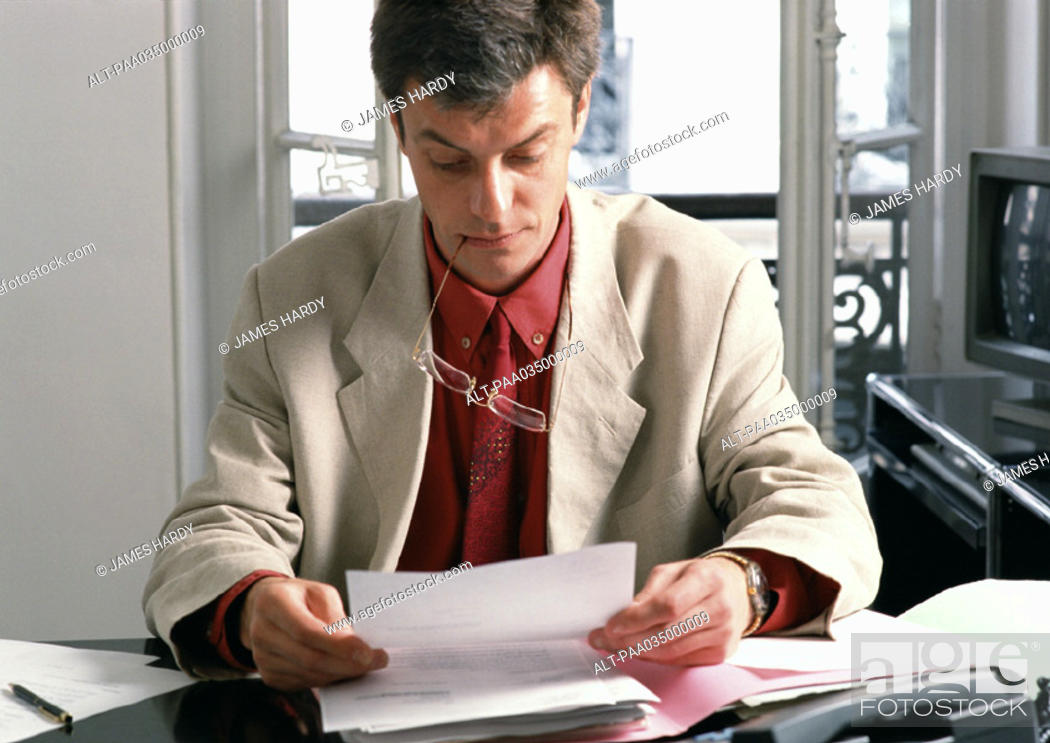 Stock Photo: Man sitting at desk, reading document.