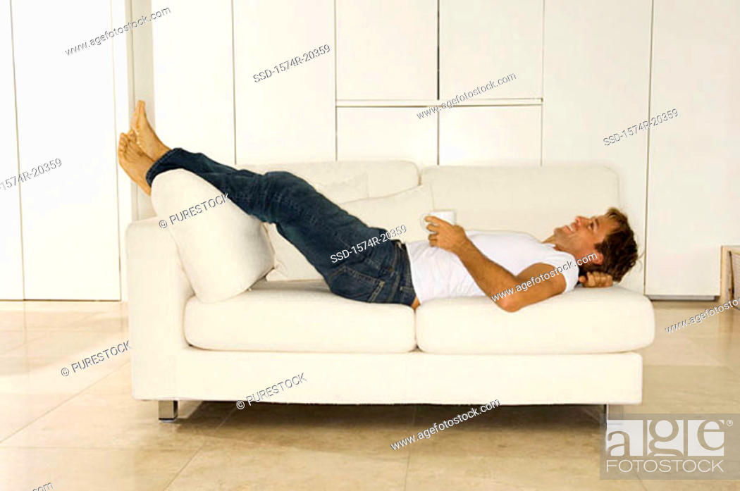 Stock Photo: Side profile of a young man lying on a couch.