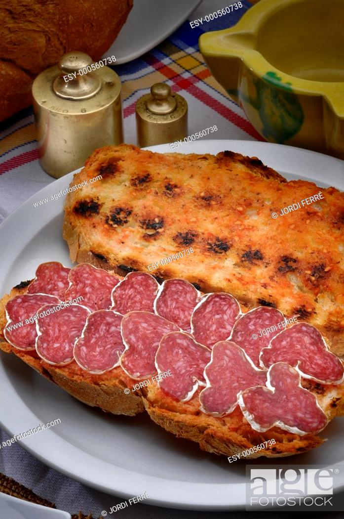 Stock Photo: Toasted bread with tomatoes and sliced cured sausage, Pan tostado con tomate y salchichón en rodajas.