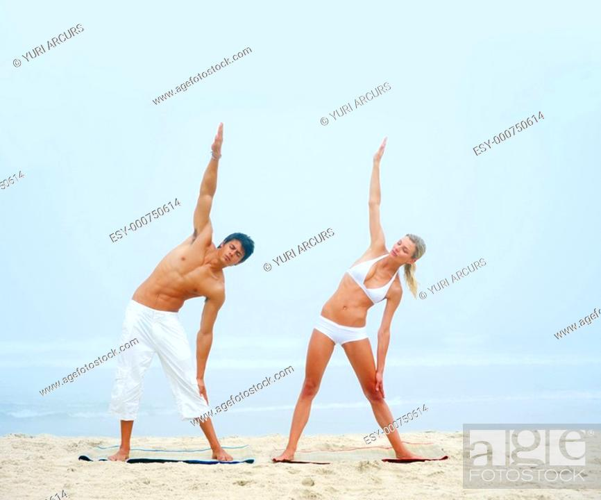 Stock Photo: Portrait of a young man and woman working out at the beach together.