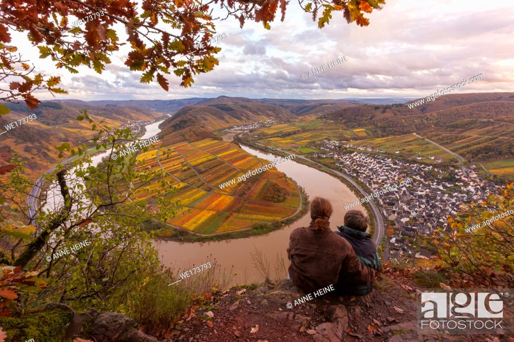 Stock Photo: Couple sitting uphill from the famous Moselschleife next to Bremm, where River Moselle makes a 180 degree turn. Lots of rain before the sun peaking through.