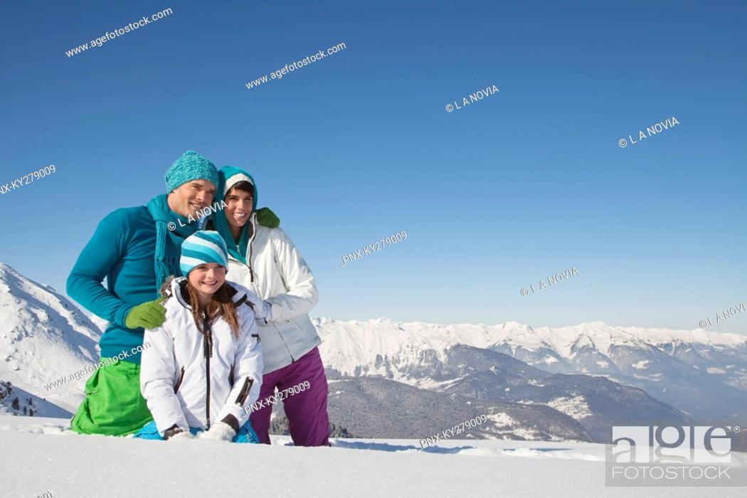 Stock Photo: Couple and daughter in ski wear, looking away.