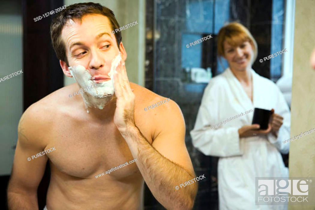 Stock Photo: Close-up of a young man applying shaving cream to his cheeks with a young woman smiling in the background.