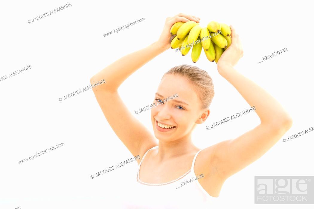 Imagen: woman helds bananas on head.
