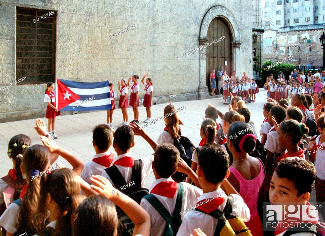 Cuban school children saluting in front of Cuban flagg, Cuba ...