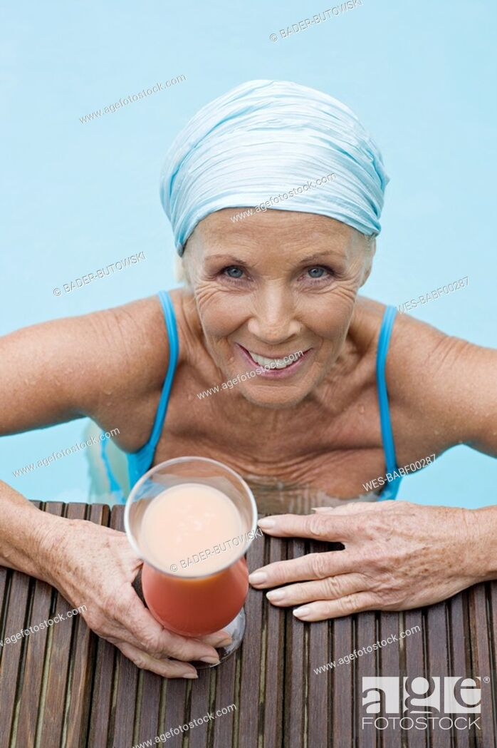 Stock Photo: Germany, senior woman having cocktail at pool.