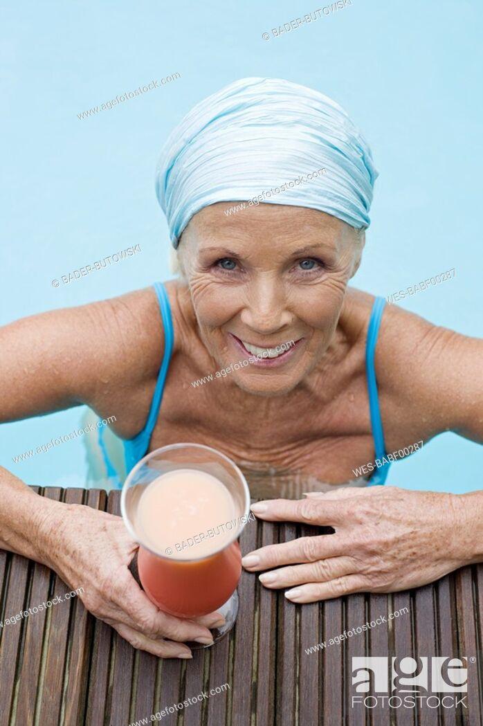 Imagen: Germany, senior woman having cocktail at pool.