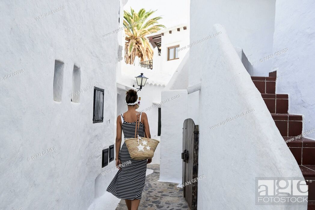 Stock Photo: Spain, Menorca, Binibequer, back view of woman walking in an alley.