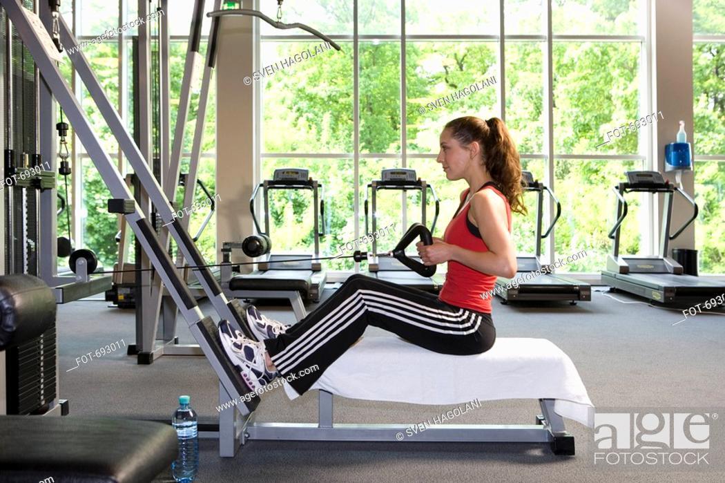 Imagen: A woman using a weight machine.