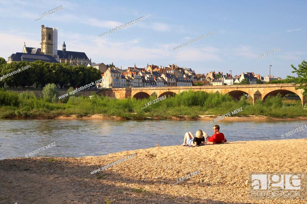 Stock Photo: Young couple sitting along the banks of the river Loire, Saint Cyr et Sainte Julitte Cathedral in the background, Bridge over the river Loire, The Way of St.