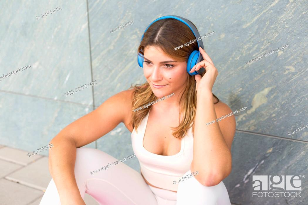 Stock Photo: Portrait of smiling young woman listening music with cordless headphones.
