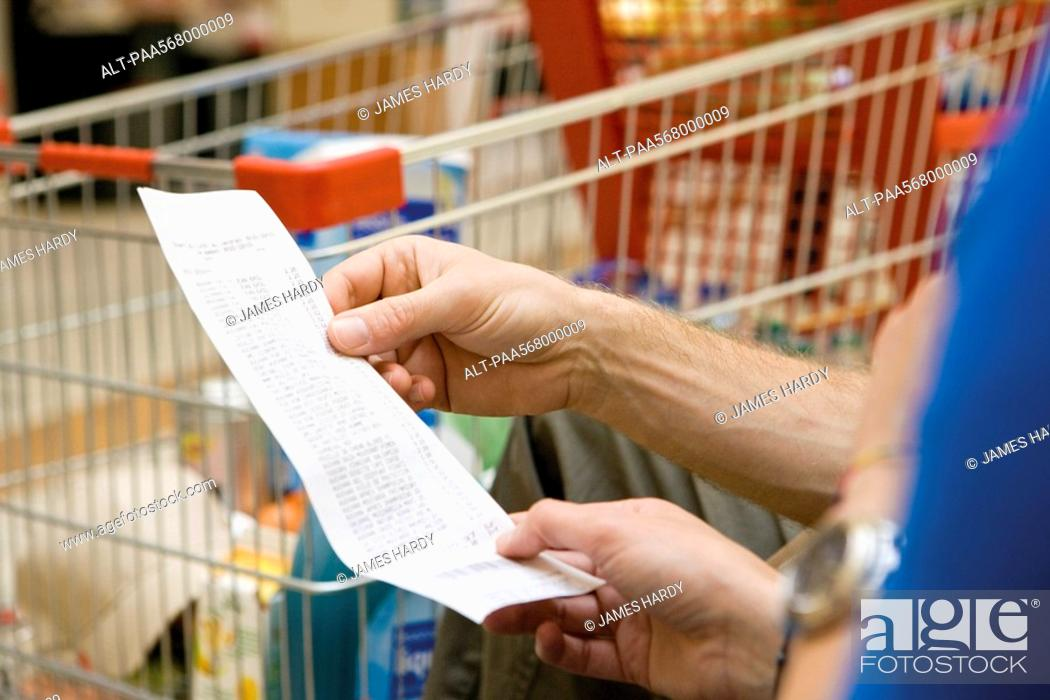Stock Photo: Shopper reviewing receipt, cropped.