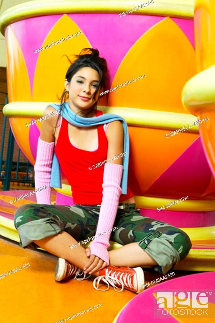Stock Photo: Hispanic teenage girl sitting next to carnival ride.