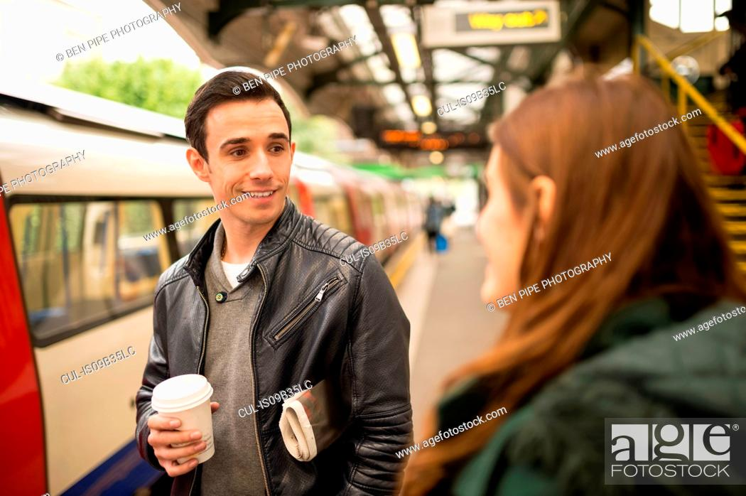 Stock Photo: Couple on railway platform face to face smiling.
