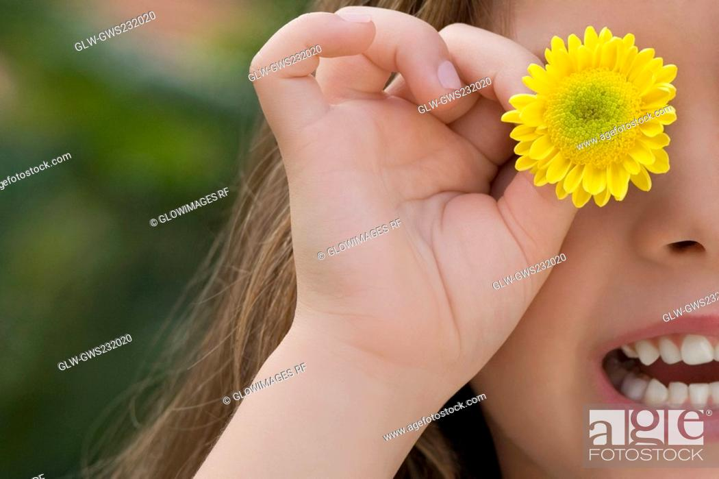 Stock Photo: Close-up of a girl holding a flower on her eye.
