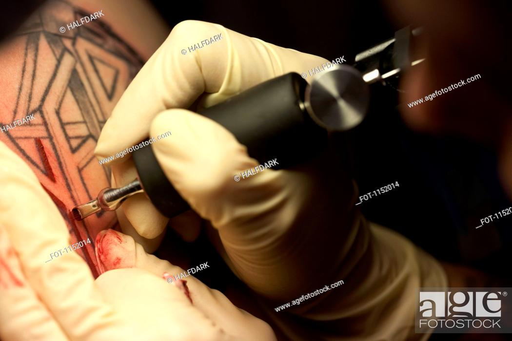 Stock Photo: Close-up of a tattoo artist tattooing a design on human skin.