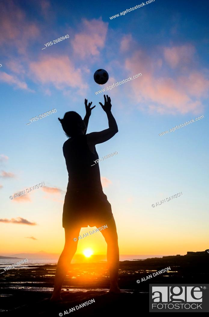 Stock Photo: Woman playing Handball at sunset on El Confital beach in Las Palmas, Gran Canaria, Canary Islands, Spain.