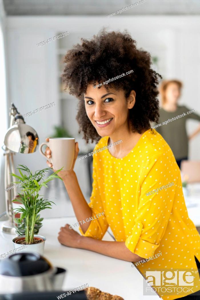 Stock Photo: Woman enjoying her coffe break in the office.
