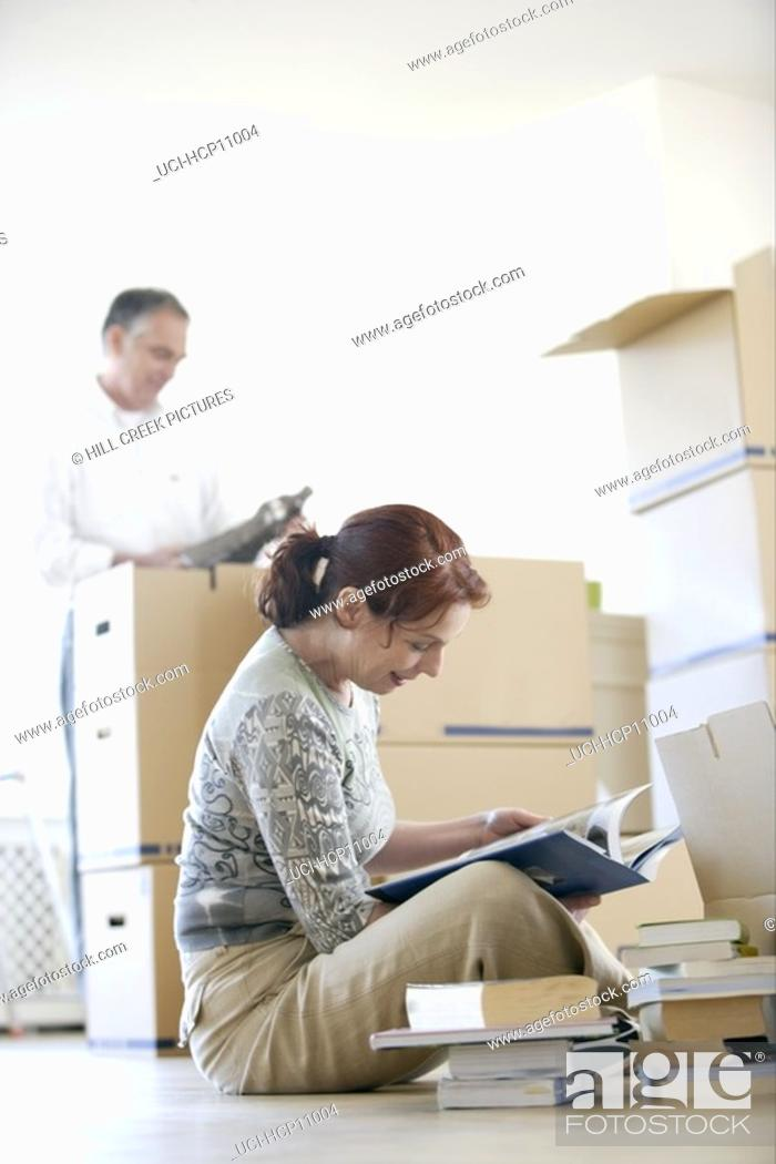 Stock Photo: Woman looking through books as she packs.