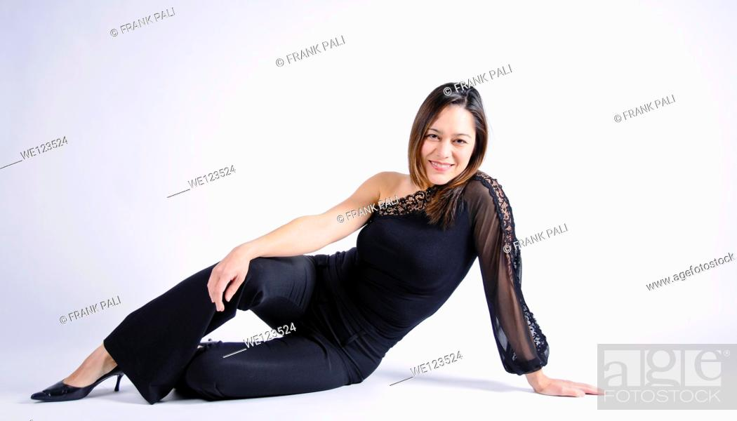 Stock Photo: Young woman of filipino ethnicity sitting sideways on a white background She has her arm on her leg.