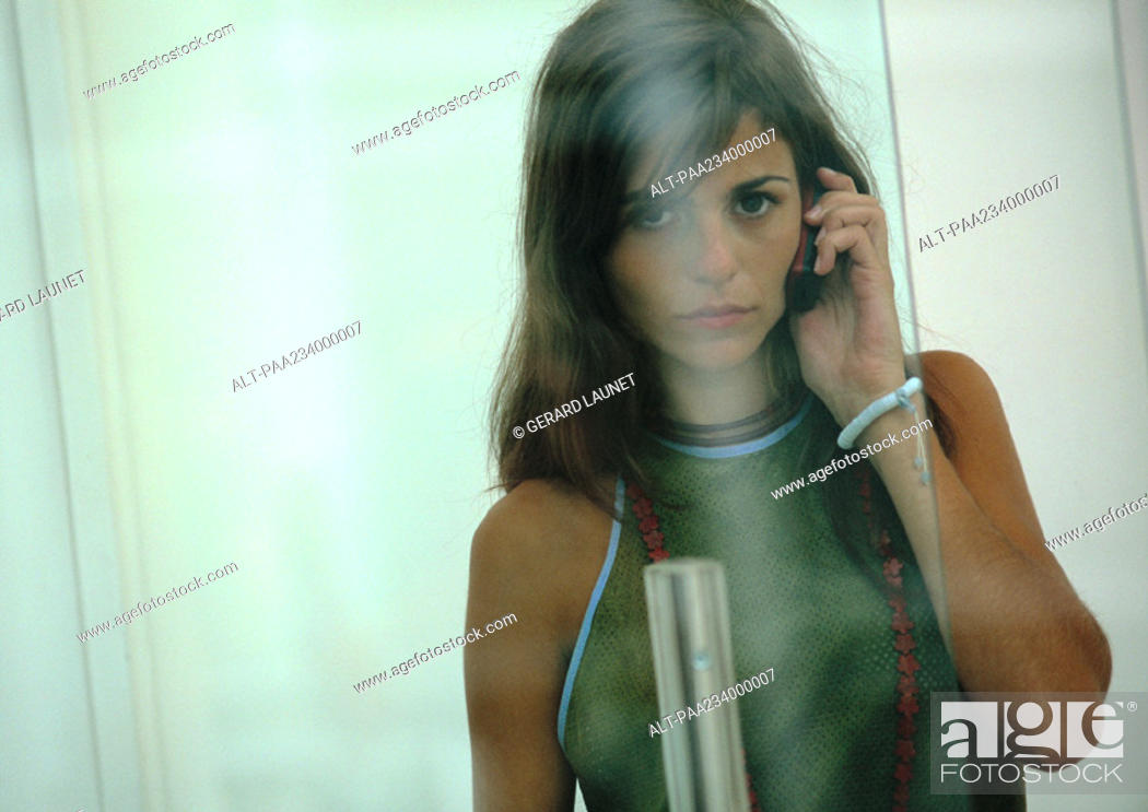 Stock Photo: Woman on cell phone, view through glass.