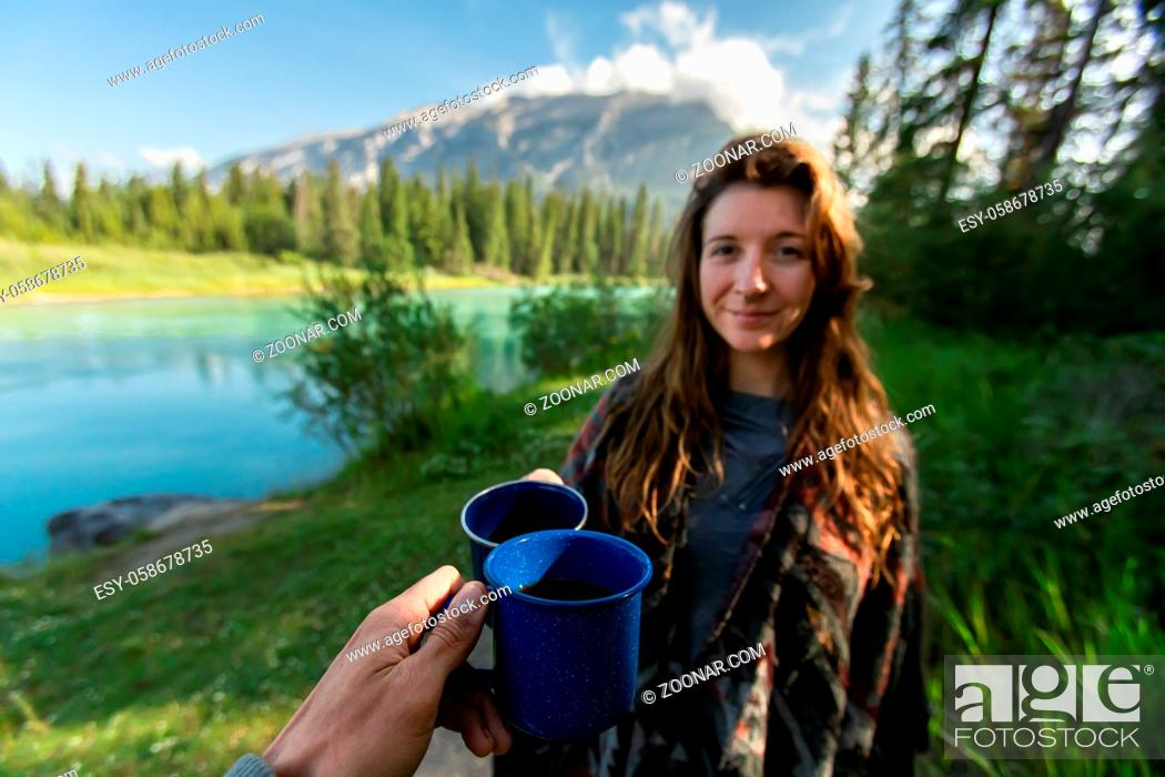 Stock Photo: Selective focus of two happy adult people spending time together in a beautiful nature reserved park drinking coffee and tea in camping style cups.