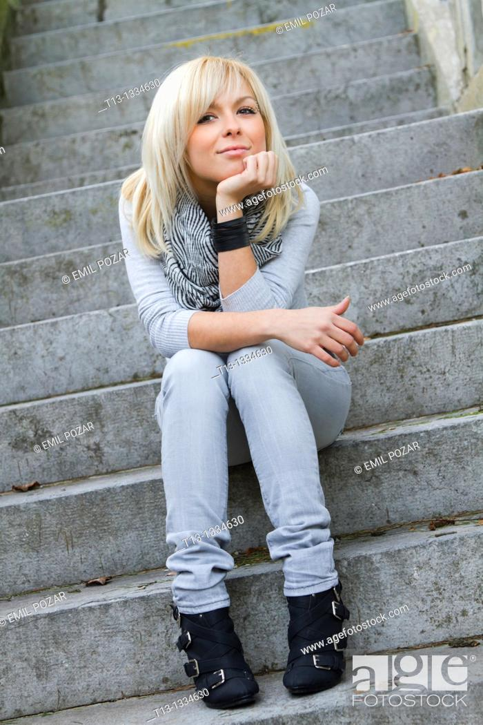 Stock Photo: Seated on a stone stairway young woman.