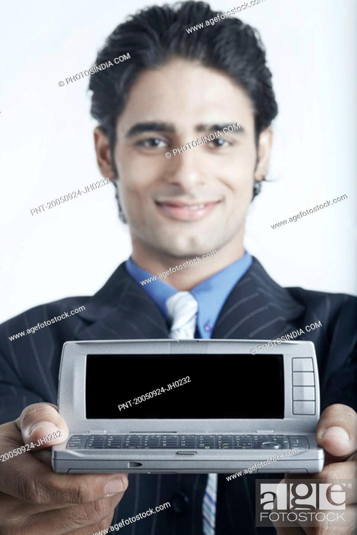 Stock Photo: Portrait of a young man holding a mobile phone.