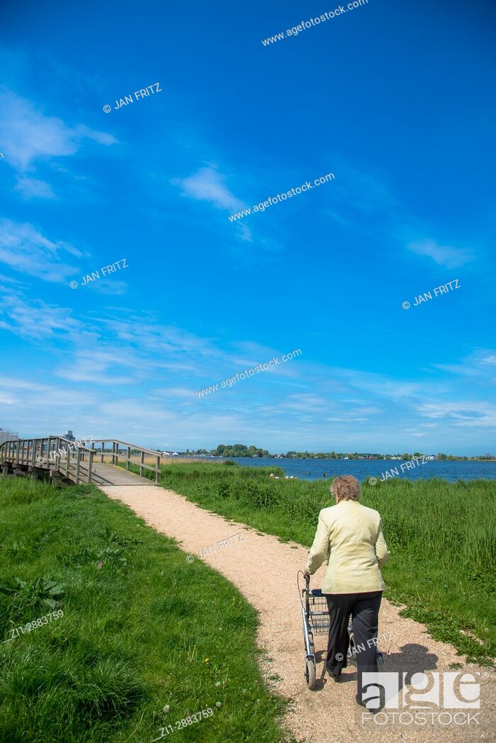 Imagen: old woman walking with help on footpath in holland.