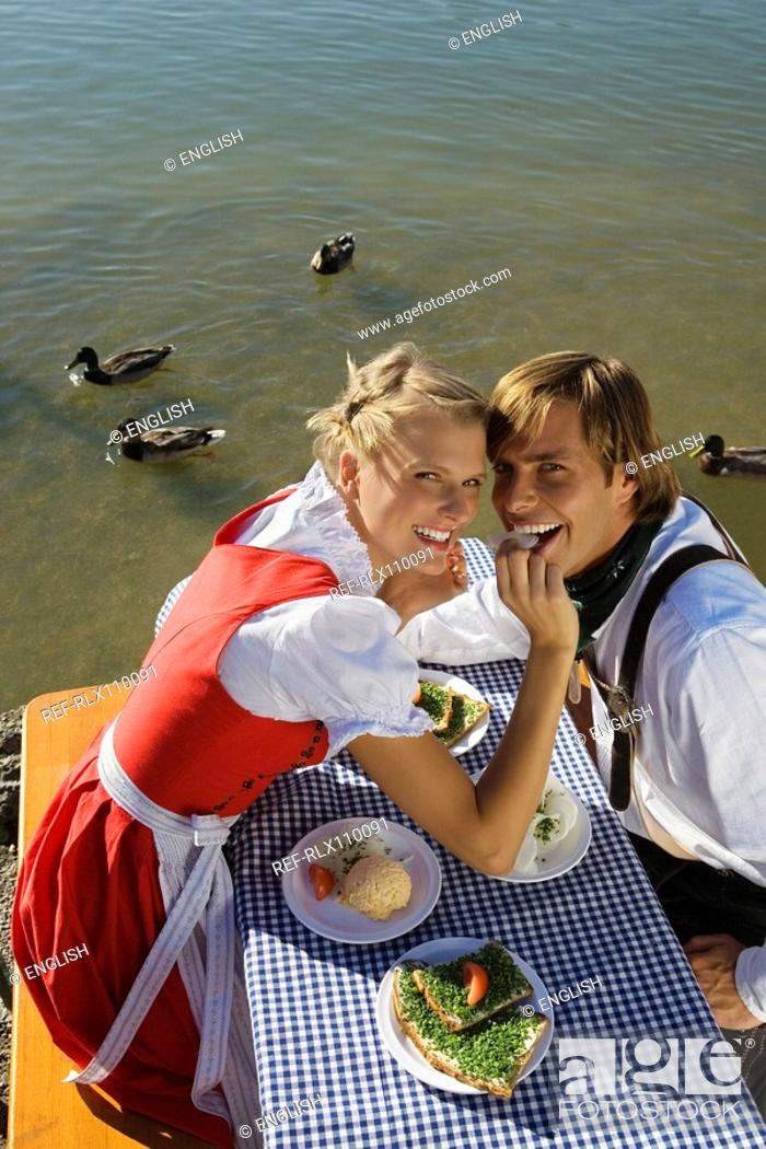 Stock Photo: Young couple in traditional Bavarian outfit, sharing meal in beer garden, Munich.