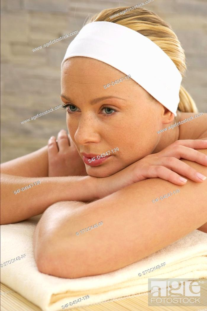 Stock Photo: Relaxed young woman lying on a towel.
