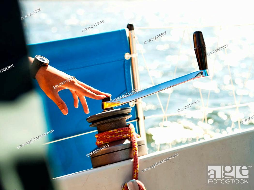 Stock Photo: Male hand on winch capstan with rope on sailing boat. Yachting yacht in blue baltic sea sunny day summer vacation. Tourism luxury lifestyle.