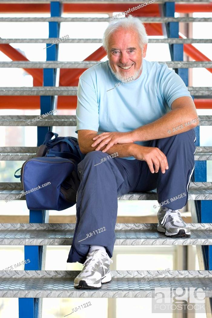Stock Photo: Senior man with gym bag on stairs, smiling, portrait.