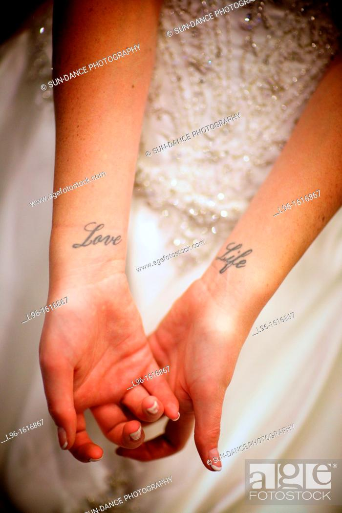 Stock Photo: bride getting ready for wedding showing 'love life' tattoo on wrists.
