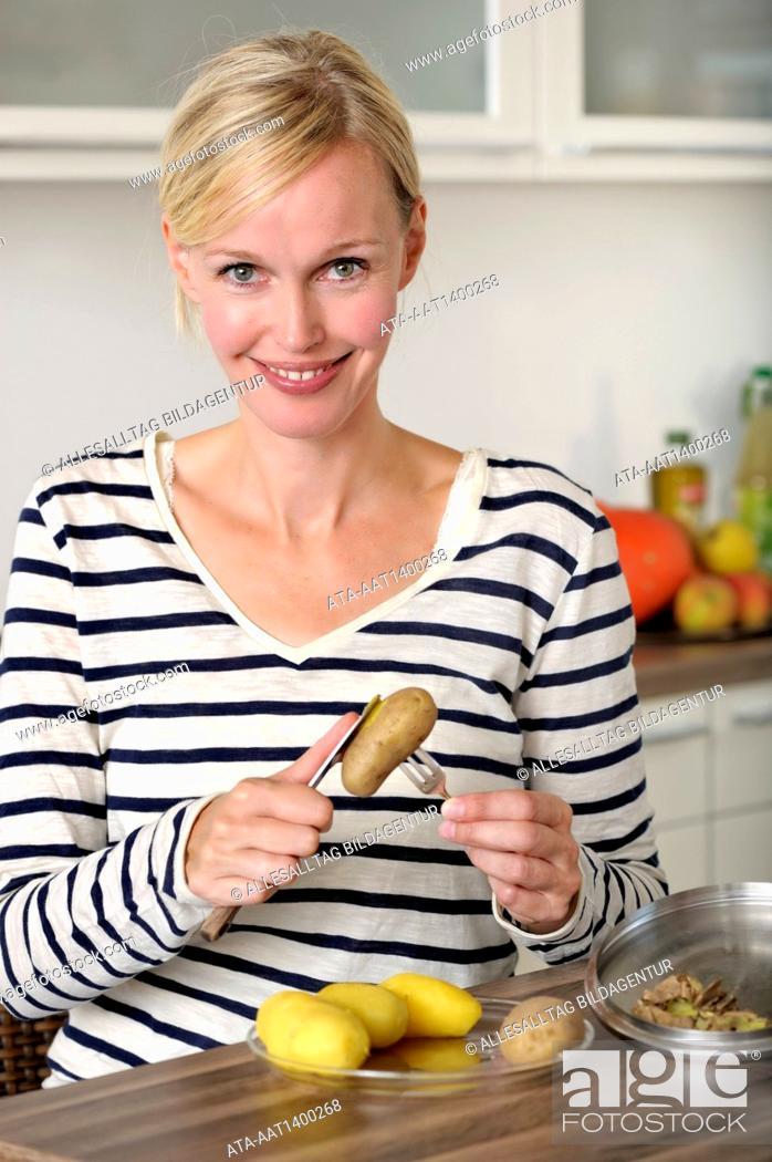 Stock Photo: Woman is peeling potatoes.