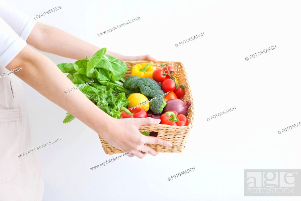 Stock Photo: Woman carrying basket with fresh vegetables.
