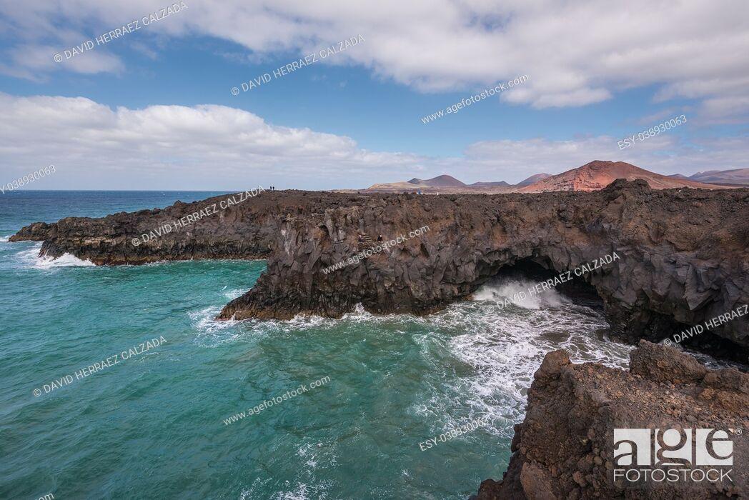 Stock Photo: Lanzarote landscape. Los Hervideros coastline, lava caves, cliffs and wavy ocean. Unidentifiable tourist are in the background.