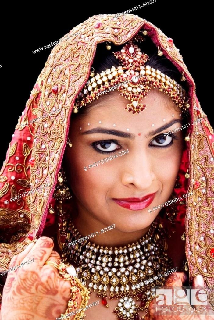Stock Photo: Close-up of a bride in a traditional wedding dress holding a veil.