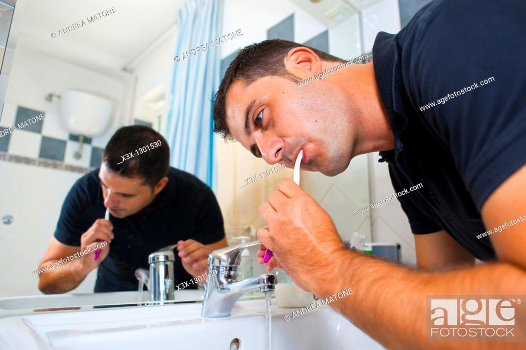 Stock Photo: Man brushing teeth in front of the mirror.