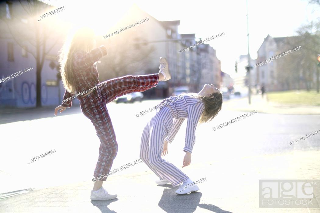 Photo de stock: two young women fighting at street, wearing pyjamas, roundhouse kick.