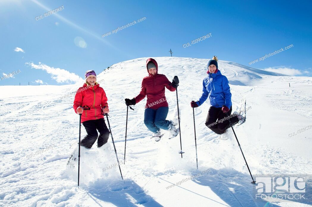 Stock Photo: Snowshoer girl and teenage sisters jumping mid air on snow covered mountainside, portrait, Styria, Tyrol, Austria.