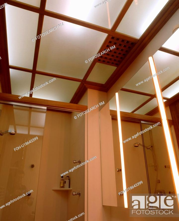 Lighted opaque glass ceiling panels in modern bathroom with strip stock photo lighted opaque glass ceiling panels in modern bathroom with strip lighting in mirrored wall aloadofball Image collections