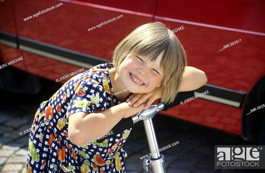 Stock Photo: A little girl, 5-10 years old, with a pedal-scooter in front of a car.
