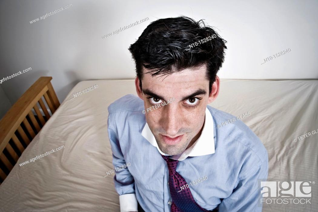 Stock Photo: Man sitting on his bed.