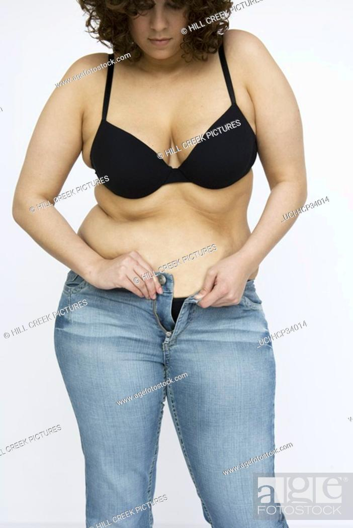 Stock Photo: Woman in bra struggling with zipper on jeans.