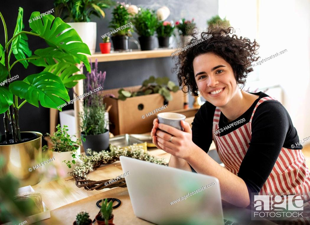 Stock Photo: Portrait of smiling young woman with coffee mug and laptop in a small shop with plants.