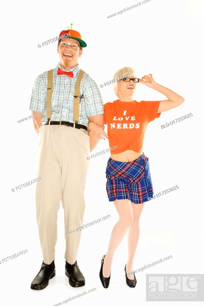 Stock Photo: Caucasian young man dressed like nerd wearing propeller hat with blonde Caucasian young woman in nerdy eyeglasses and tshirt reading I love nerds and plaid.