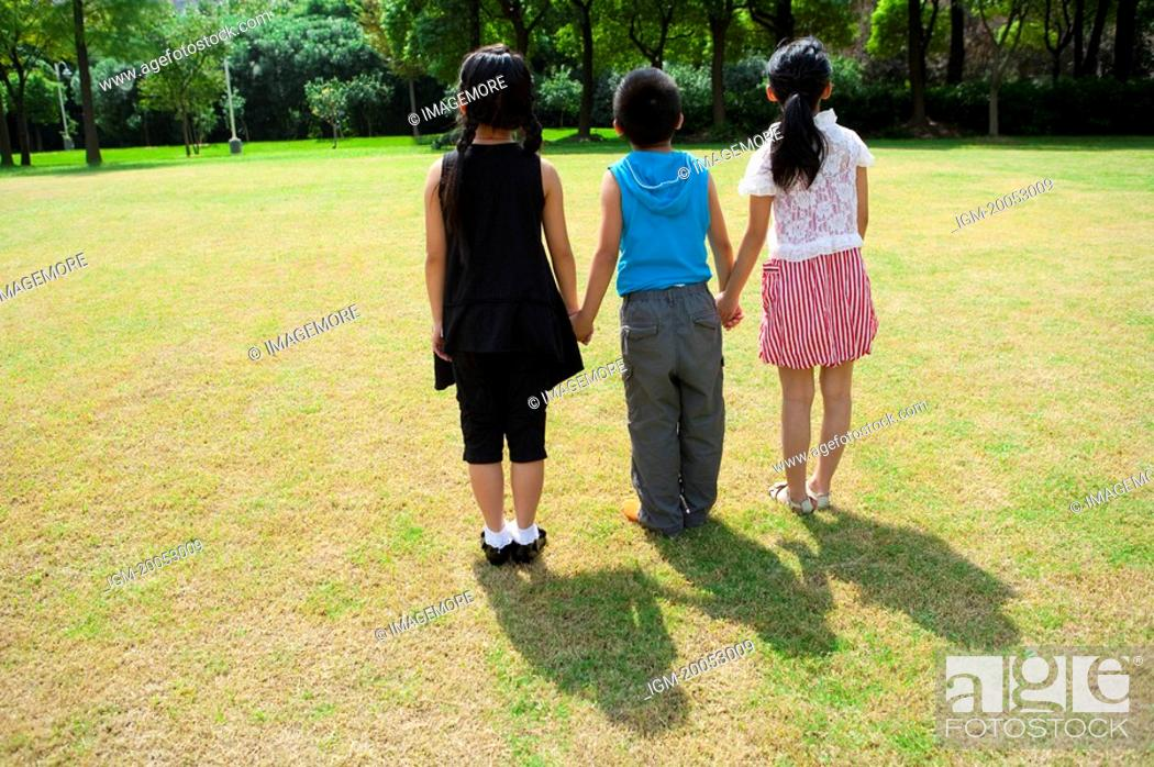 Stock Photo: Three children holding hands together and standing in a row.